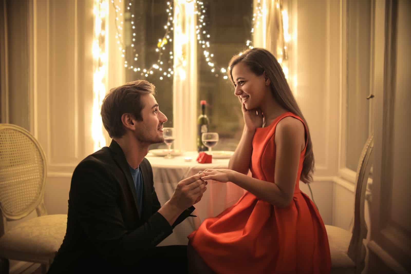 Hübscher Mann, der eine schöne Frau vorschlägt, um ihn in einem eleganten Restaurant zu heiraten