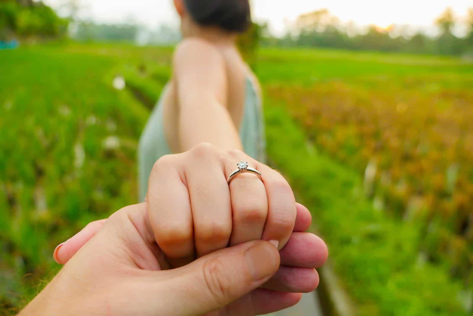 Mann, der glückliche Verlobte Hand mit Diamant-Verlobungsring hält