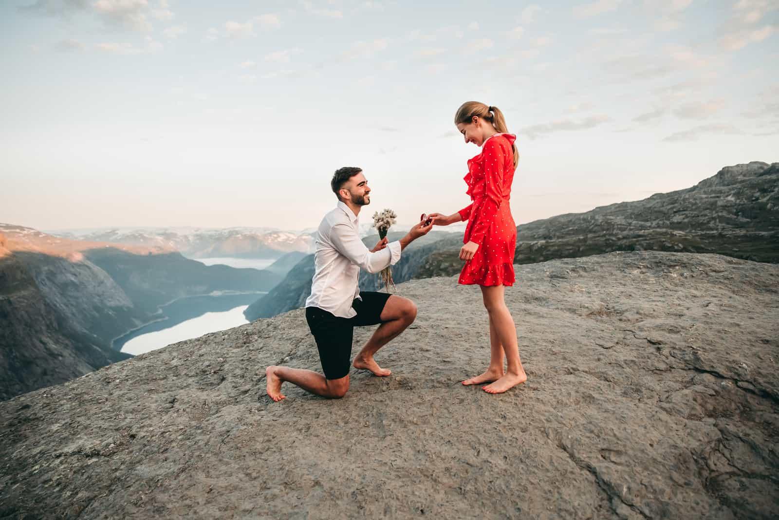 Mann steht auf seinem Knie in der Nähe der Klippe und macht einen kreativen Vorschlag