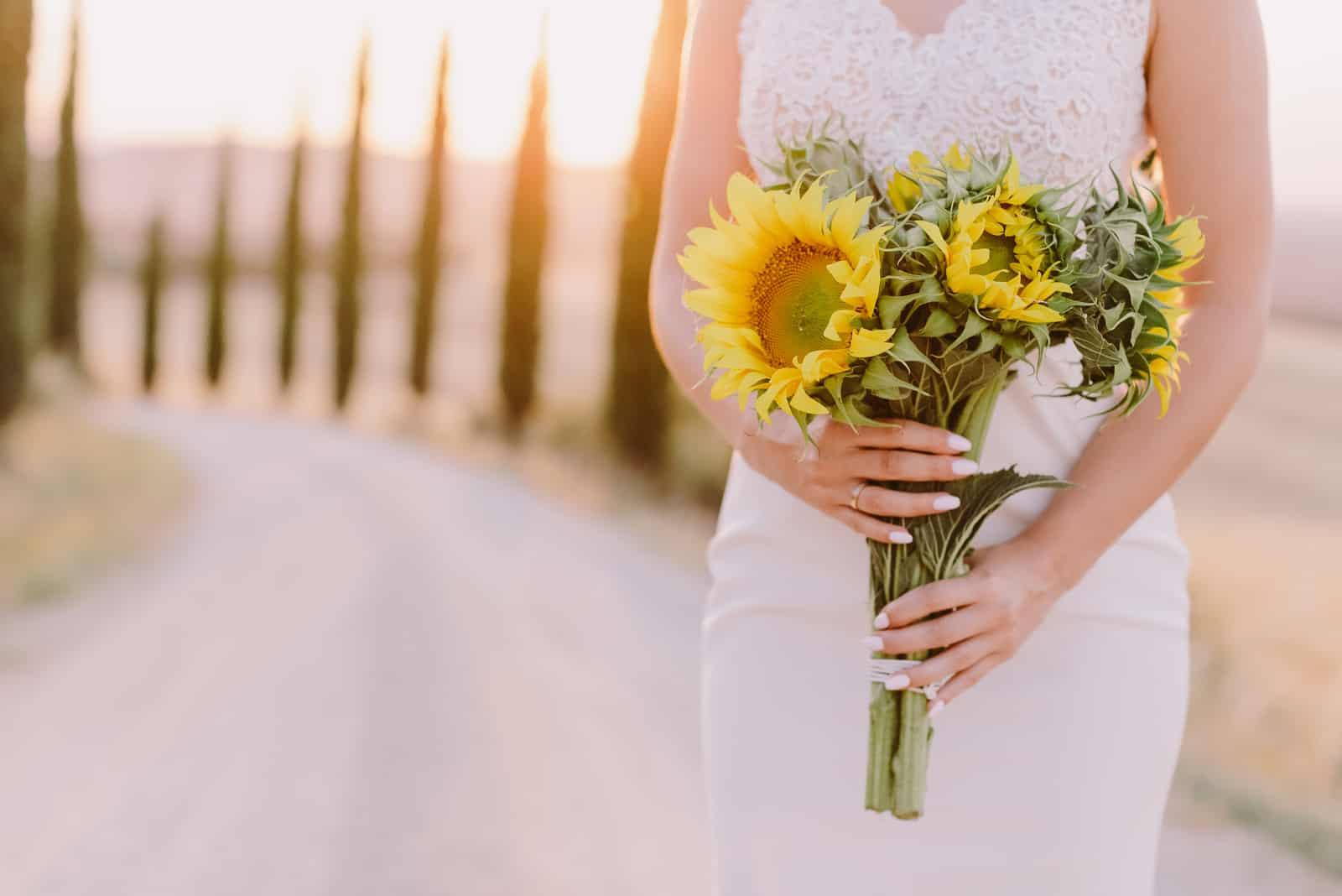 Sonnenblumenstrauß, der durch Braut hält