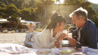 Ehepaar mittleren Alters, das am Strand liegt und einen Toast macht