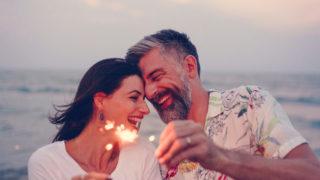 Paar feiert mit Wunderkerzen am Strand