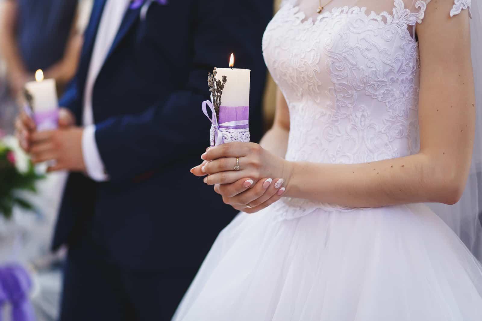 Braut und Bräutigam halten Kerzen in der Kirche