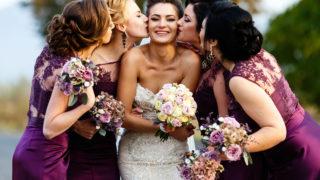 Brautjungfern küssen schöne Braut draußen stehend