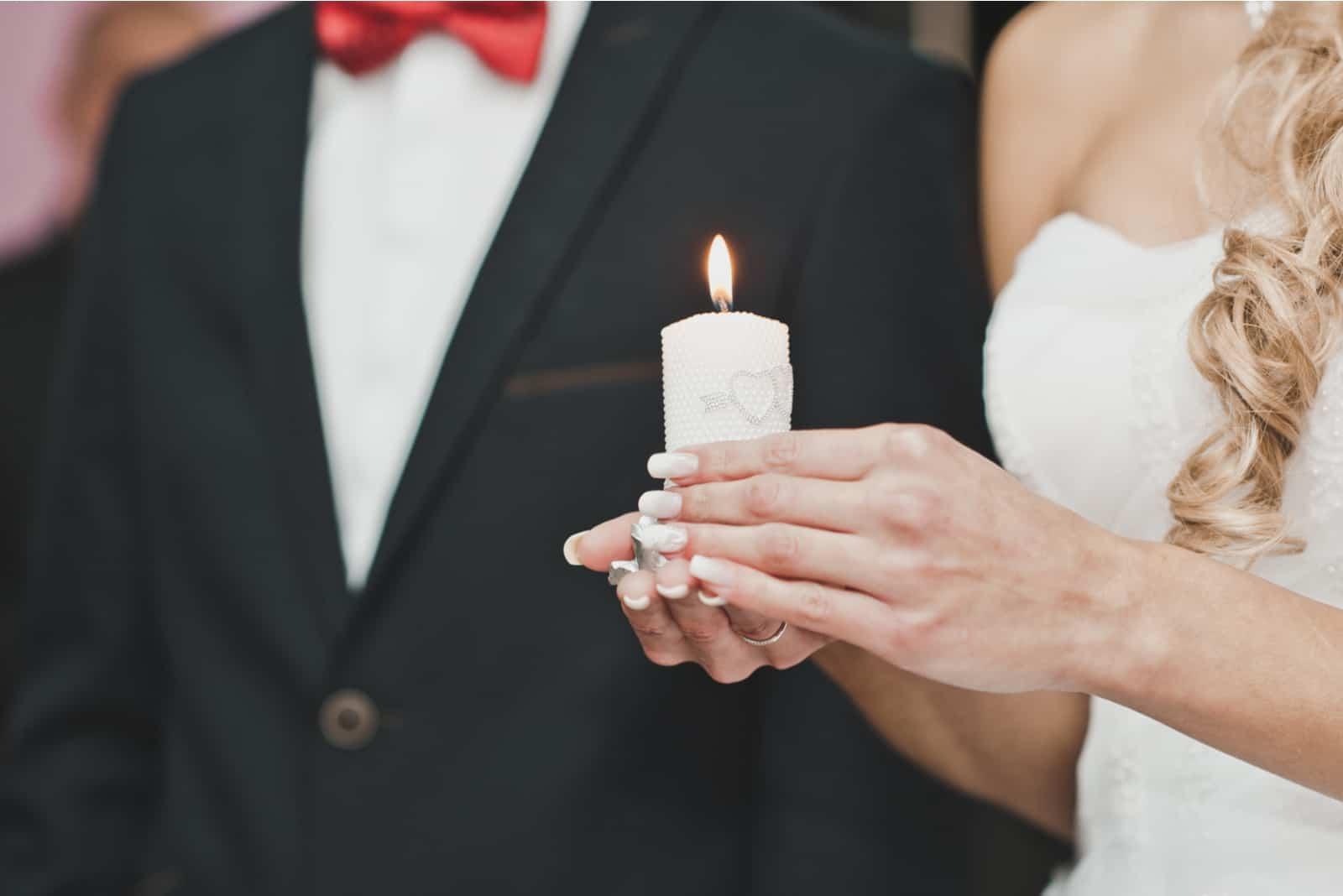 Die Braut hält eine Kerze