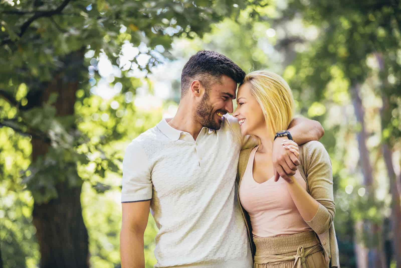 Glückliches verliebtes Paar, das im Park spazieren geht