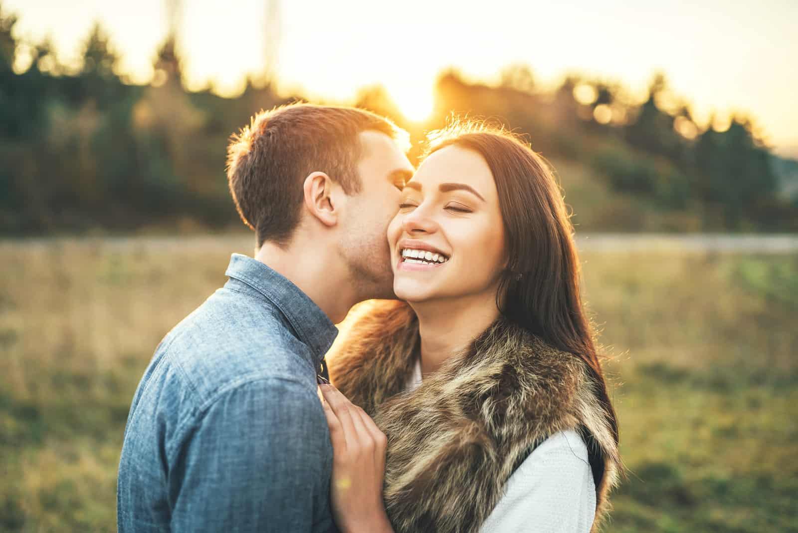 Glückliches verliebtes Paar, das sich auf dem Feld entspannt