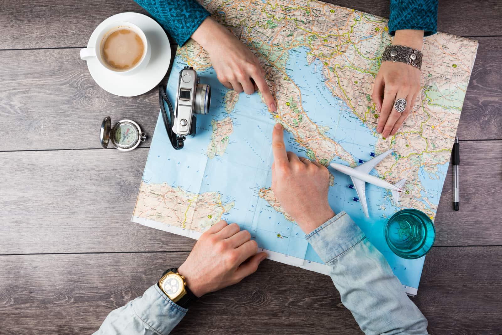 Junges Paar plant Flitterwochen-Urlaubsreise mit Karte