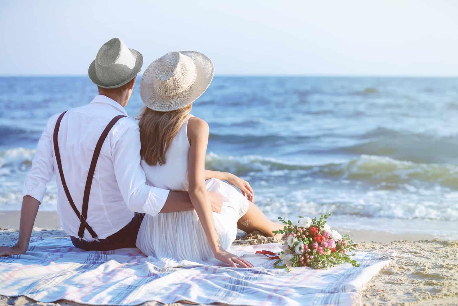 Junges glückliches Paar sitzt zurück am Strand