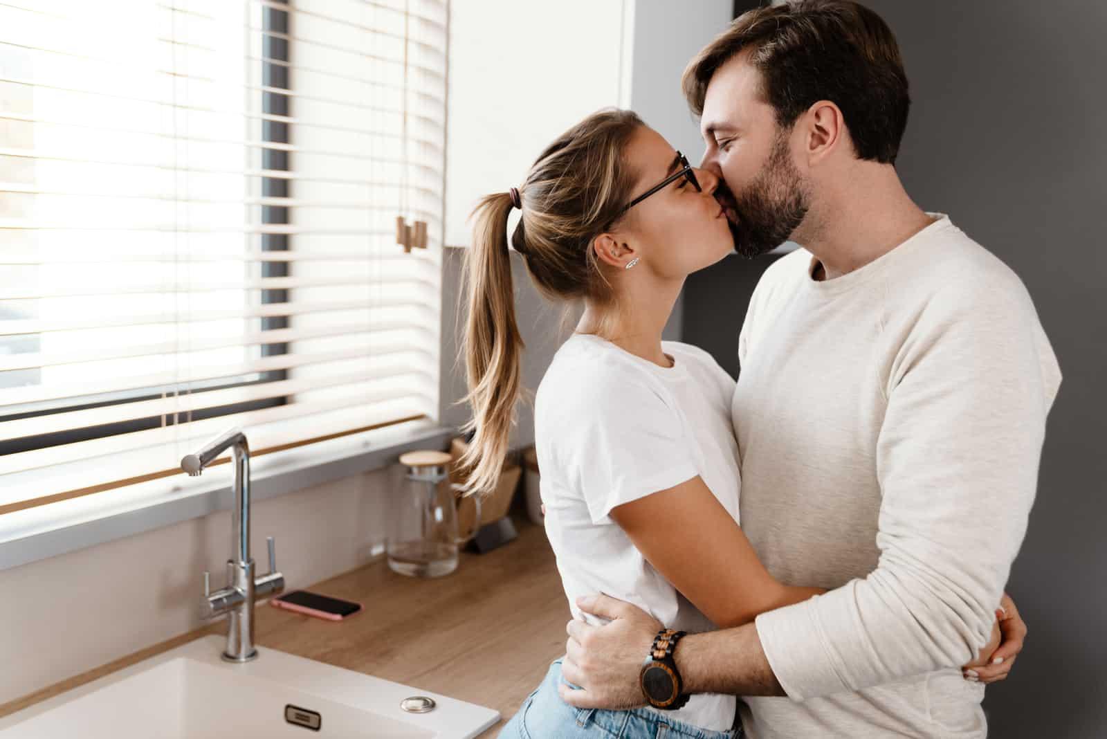 Paar küssen und umarmen sich zu Hause in der Küche
