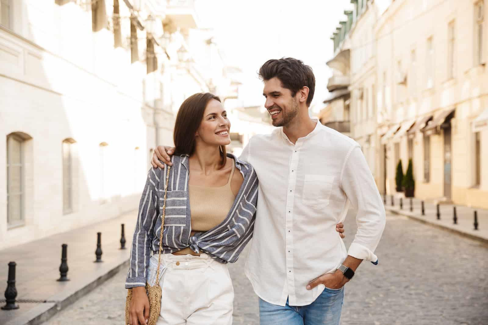 Paar lächelt und umarmt beim Gehen auf der Stadtstraße