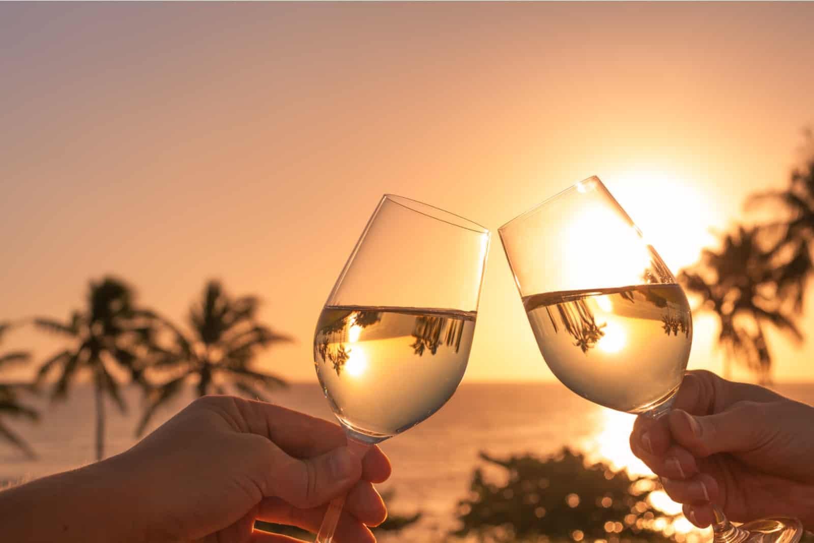 Prost mit Weingläsern bei einem wunderschönen Sonnenuntergang
