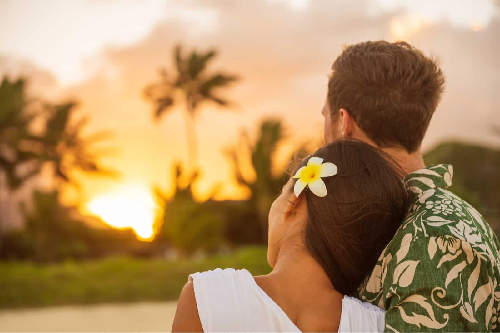 Romantisches Paar entspannt den Sonnenuntergang am Strand beobachten