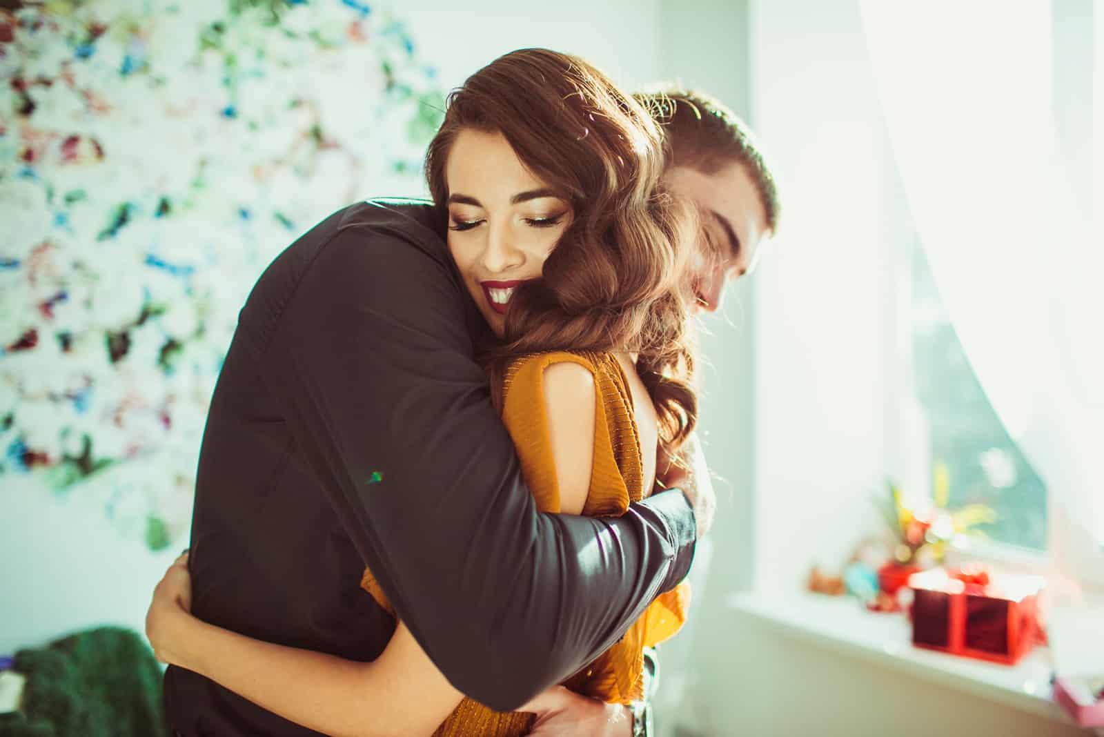 Schöne Dame lehnt sich an die Schulter des Mannes, während er sie umarmt