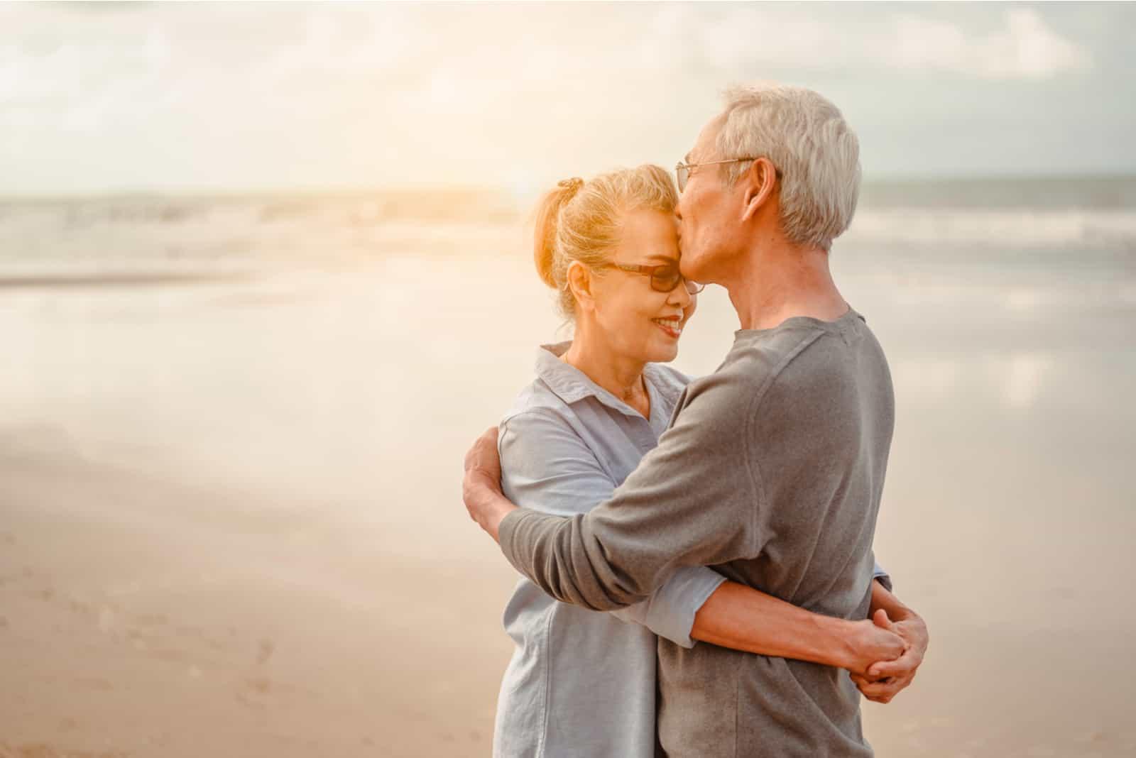 Seniorenliebende umarmen und küssen sich im Sonnenuntergang am Strand