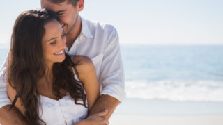 Attraktives Paar beim Kuscheln am Strand