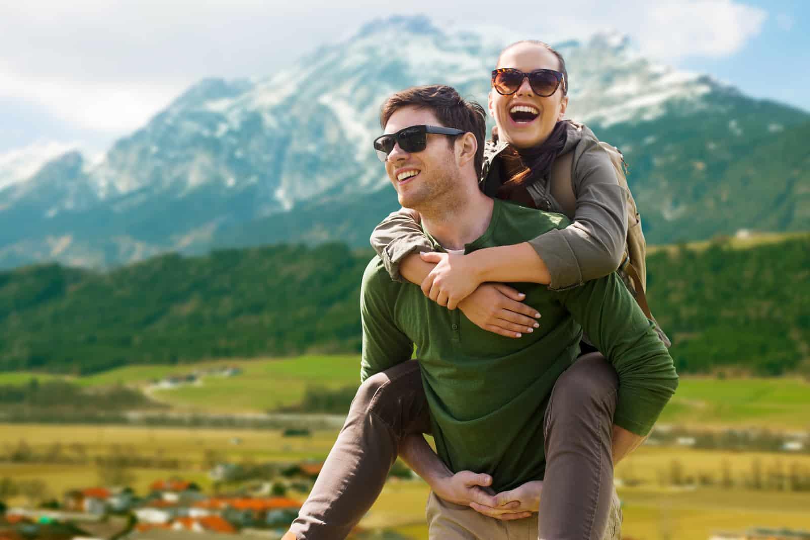 glückliches Paar mit Rucksäcken, das Spaß über den Alpenbergen hat_