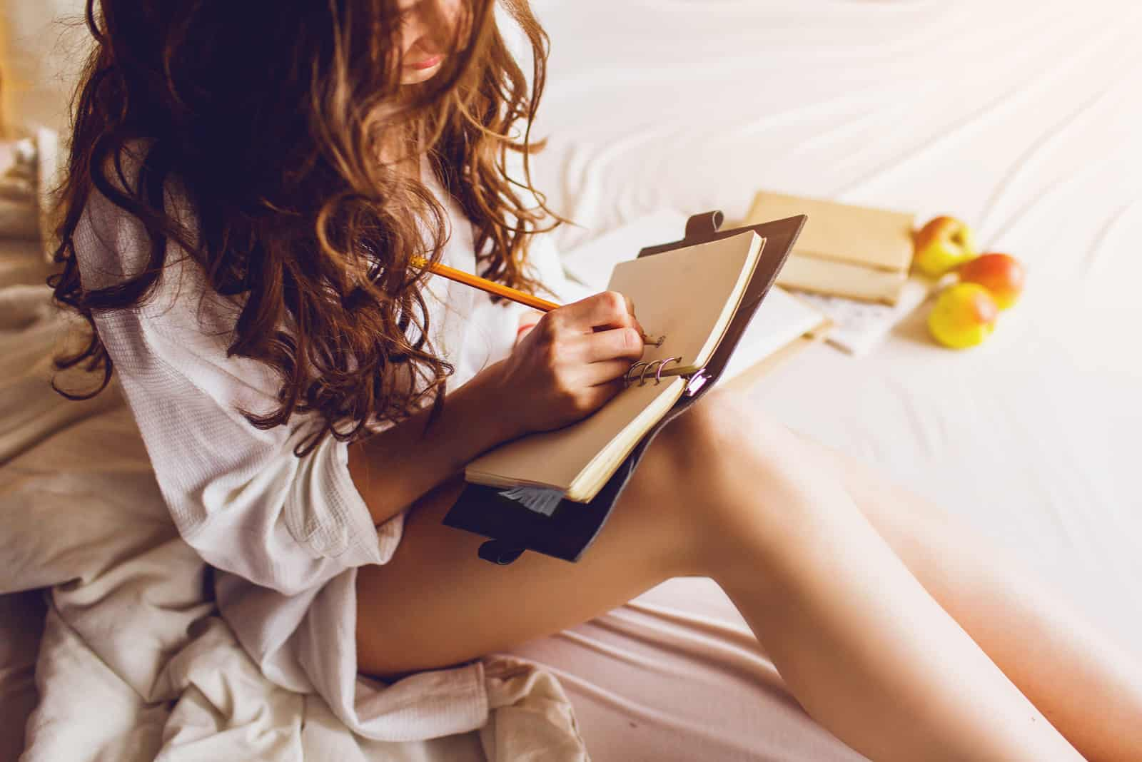 hübsche junge Frau sitzt auf ihrem gemütlichen Bett und macht sich Notizen zu ihrem Tagebuch