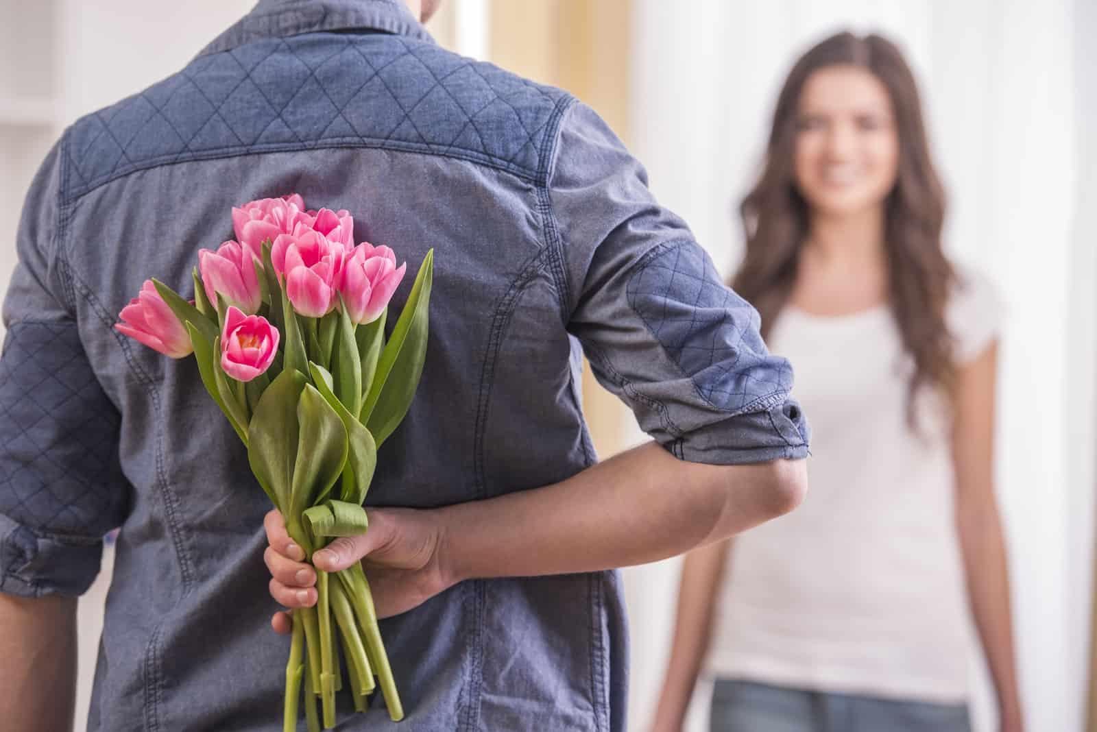 junger Mann versteckt Blumen hinter seinem Rücken