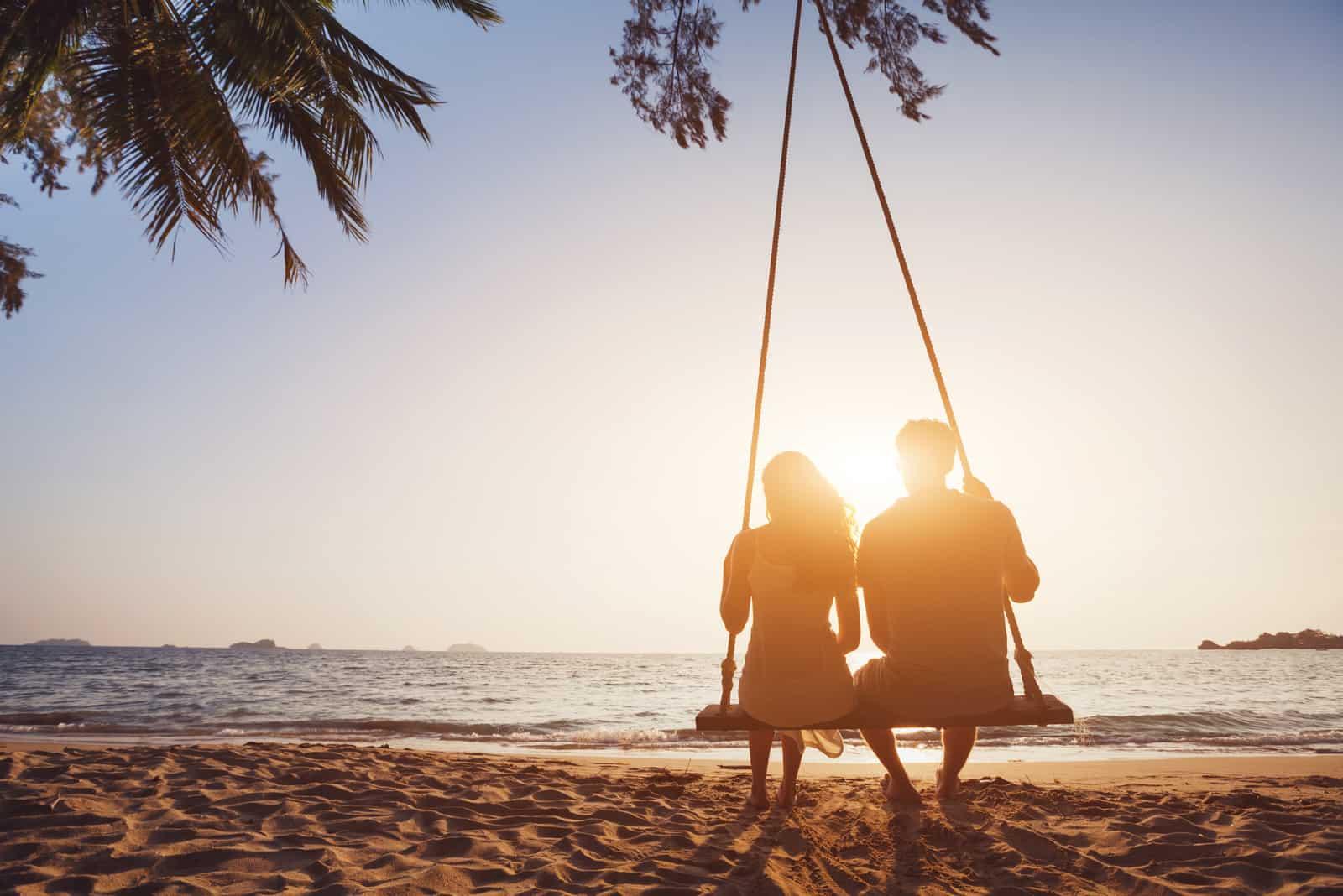 romantisches verliebtes Paar, das zusammen auf Seilschaukel am Sonnenuntergangstrand sitzt