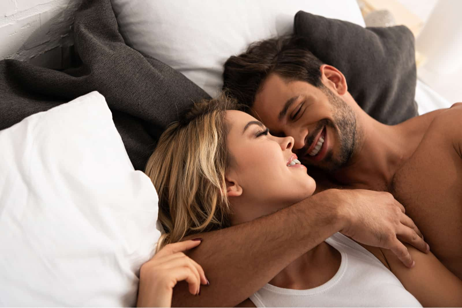 zartes Paar, das sich morgens im Bett umarmt