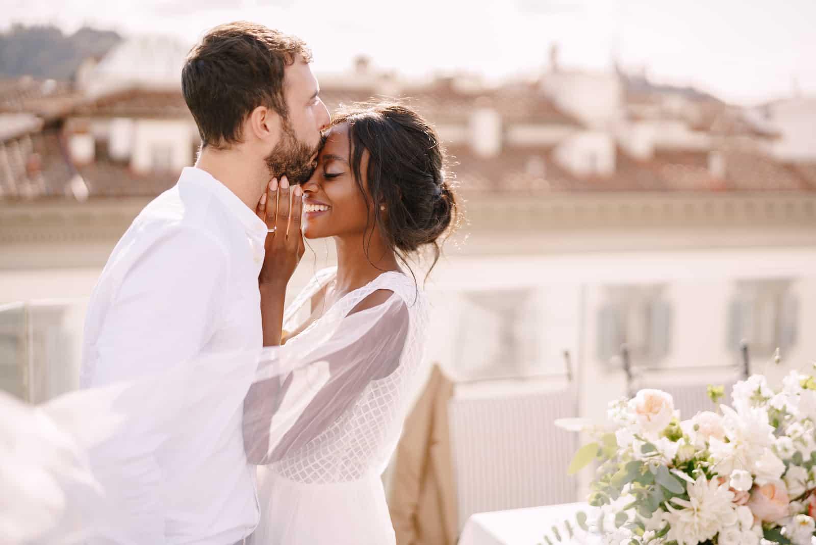 Bräutigam und Braut kuscheln auf einem Dach im Sonnenuntergangssonnenlicht