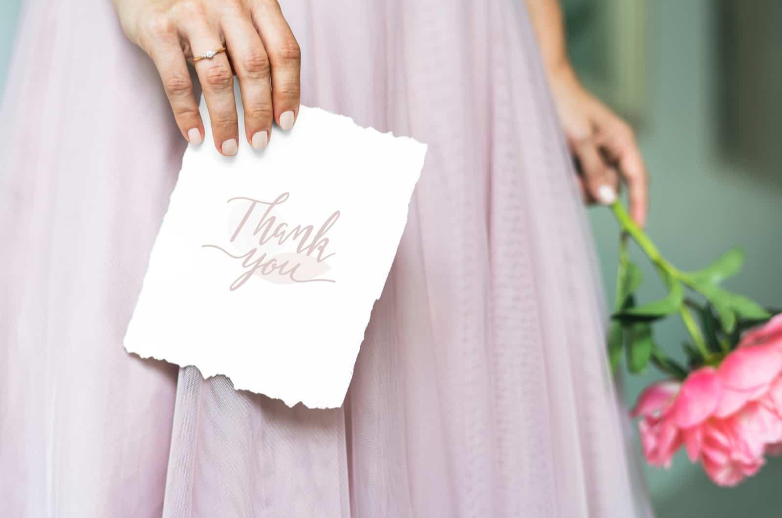 Braut hält eine Dankeskarte