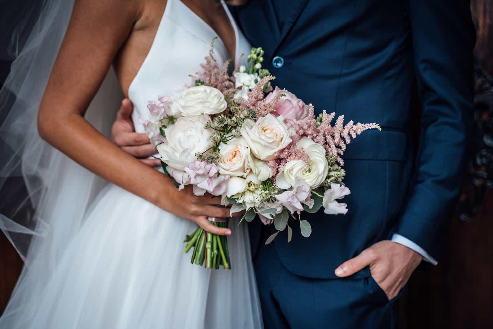 Braut mit Hochzeitsstrauß aus weißen und rosa Rosen