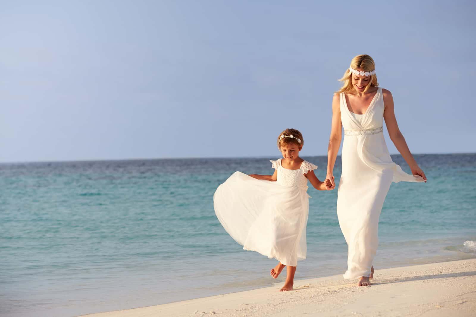 Braut mit kleinem Mädchen, das am Strand spazieren geht