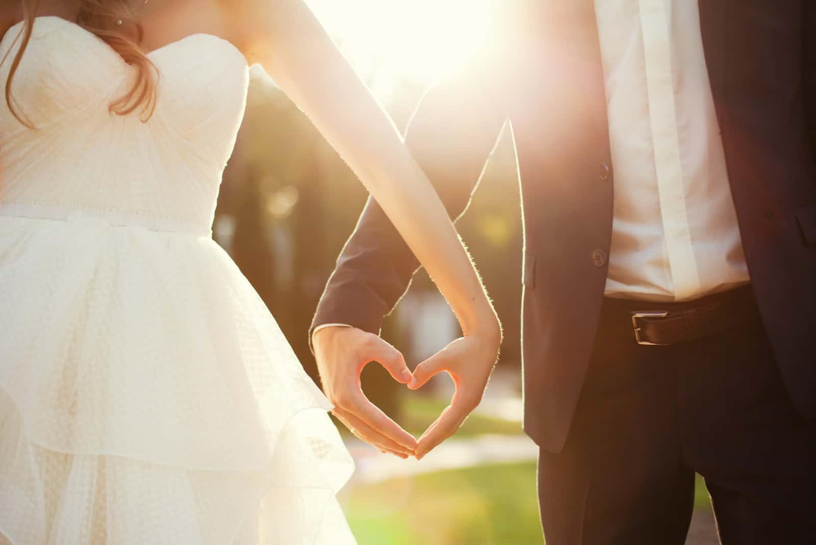 Braut und Bräutigam halten sich an den Händen in Herzform