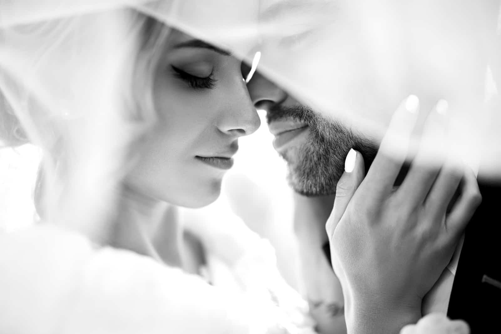 Braut und Bräutigam kuscheln im Schatten eines fliegenden Schleiers