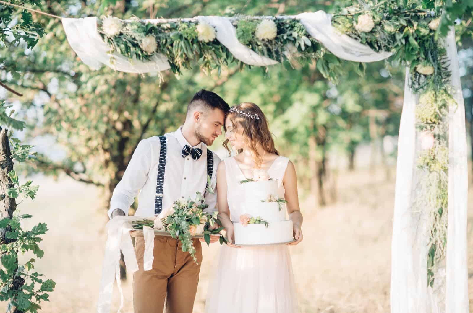 Braut und Bräutigam posieren mit ihrer Hochzeitsdekoration