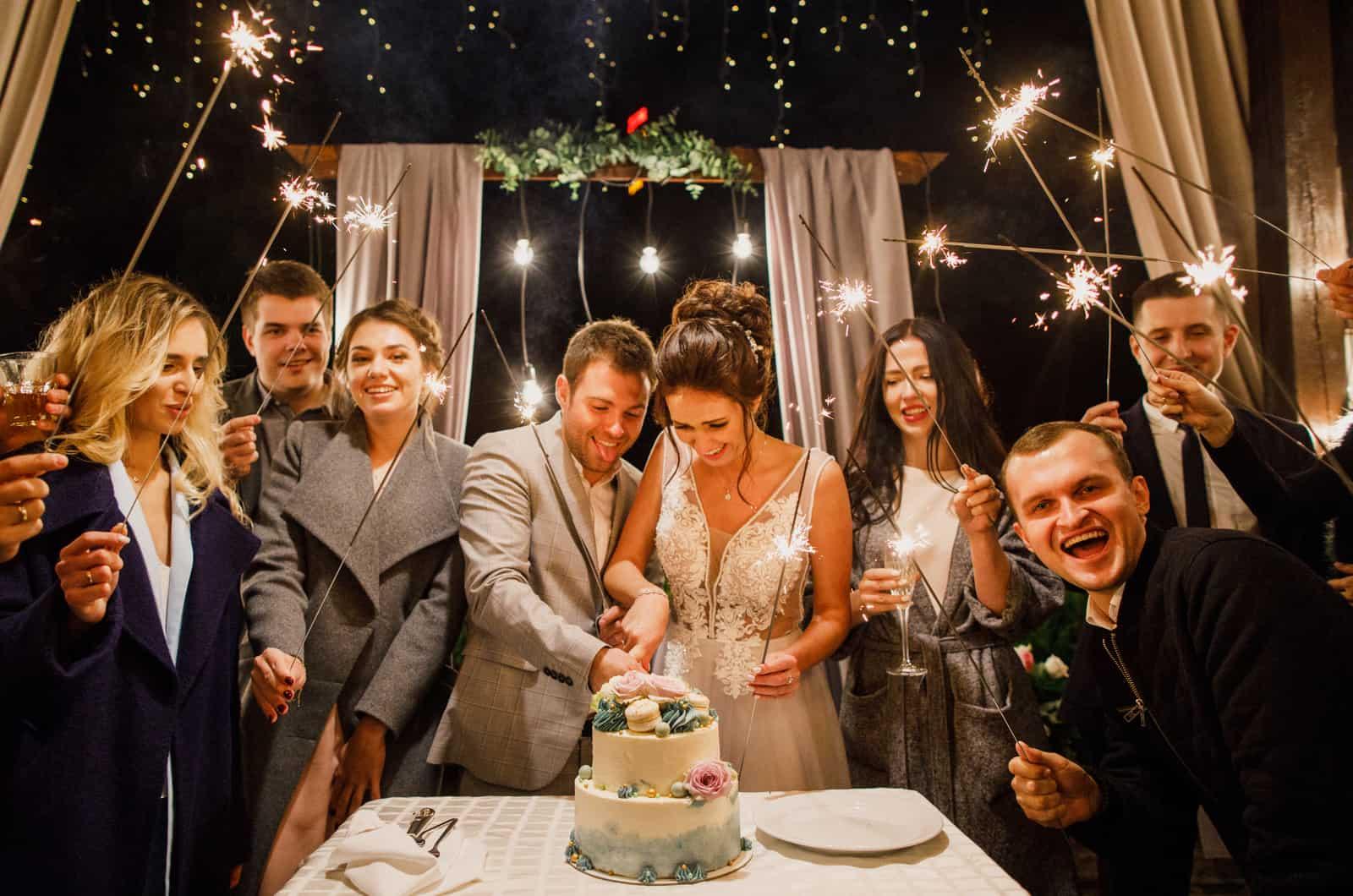 Braut und Bräutigam schneiden einen Kuchen, umgeben von Freunden