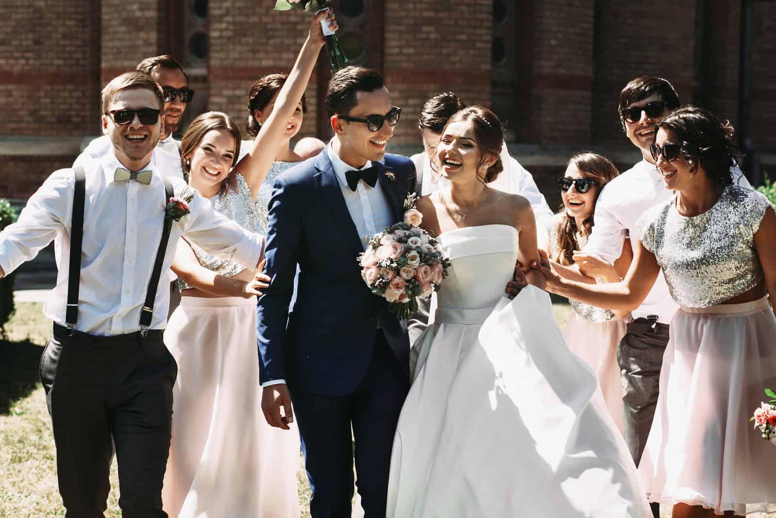 Brautpaar, Brautjungfern und Trauzeugen haben Spaß im Freien