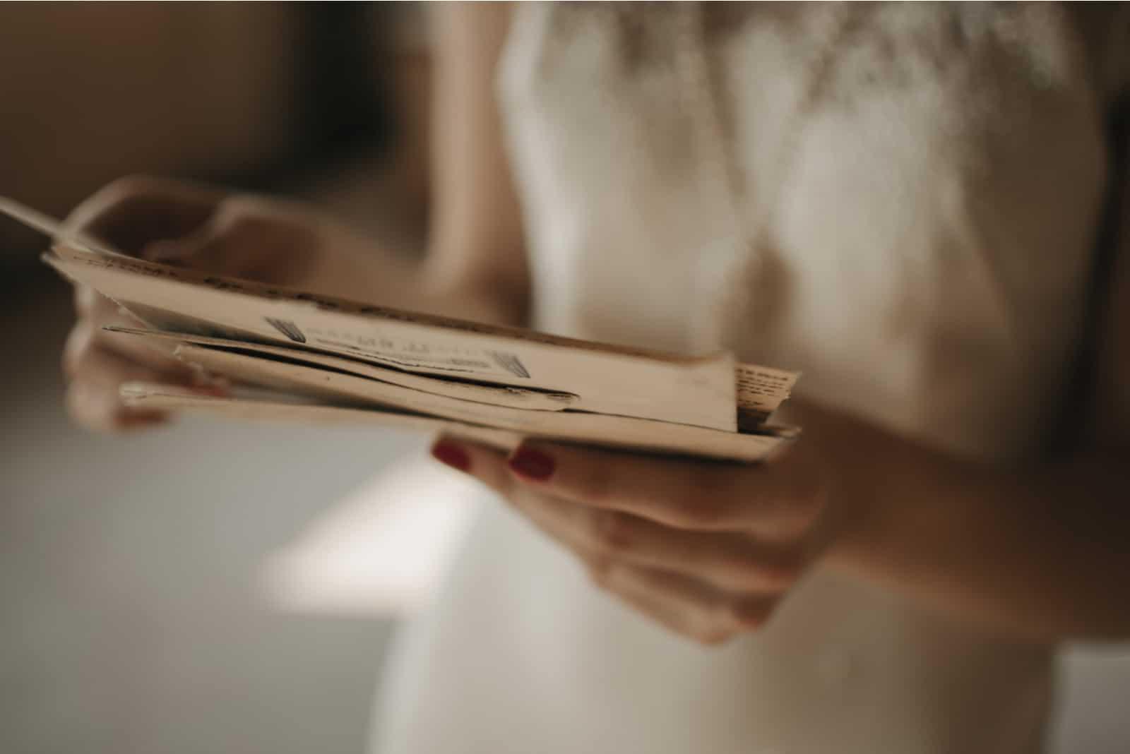 Ein Mädchen, das einen Stapel alter Briefe hält