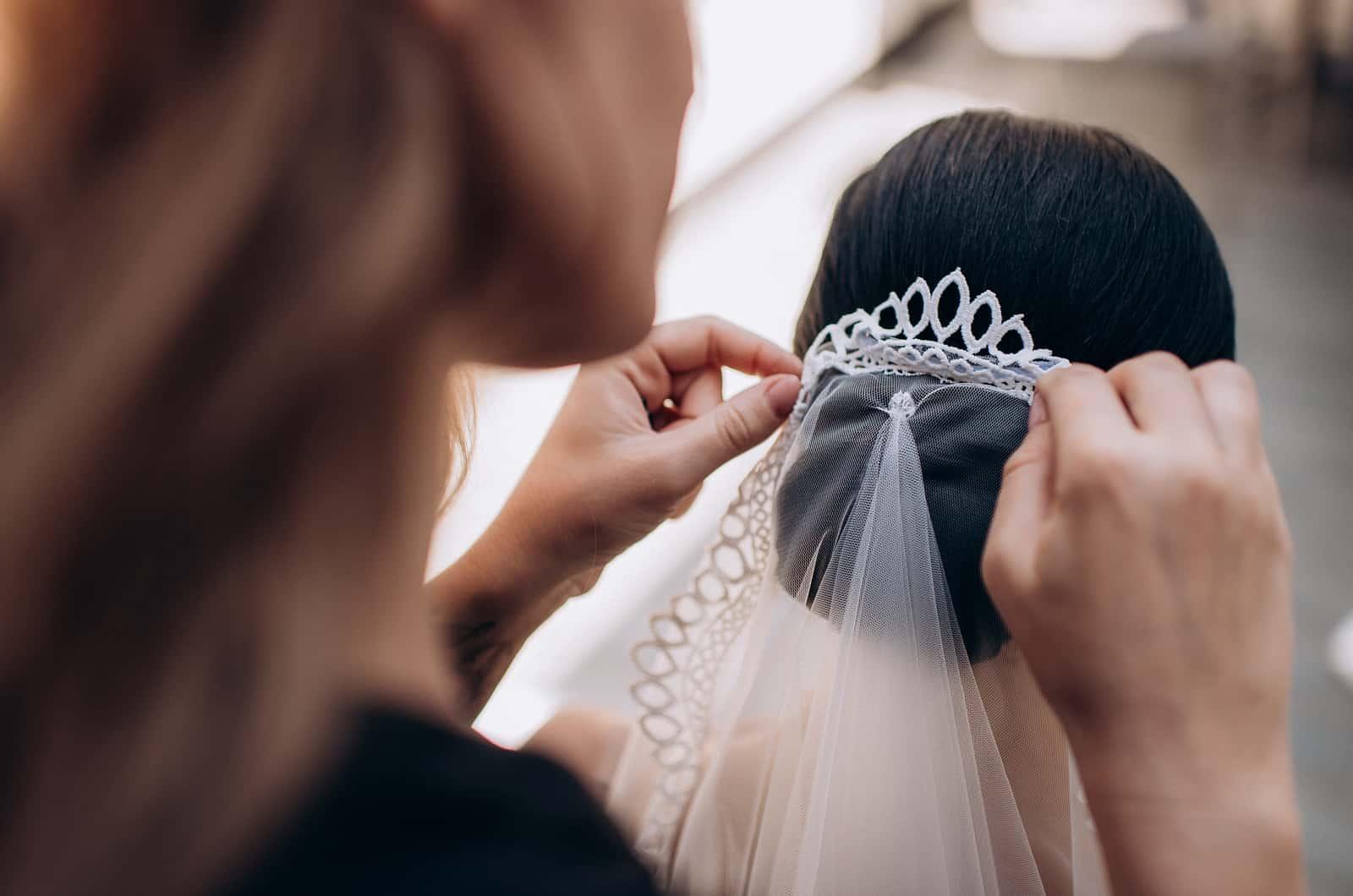 Frau legt der Braut einen Schleier ins Haar