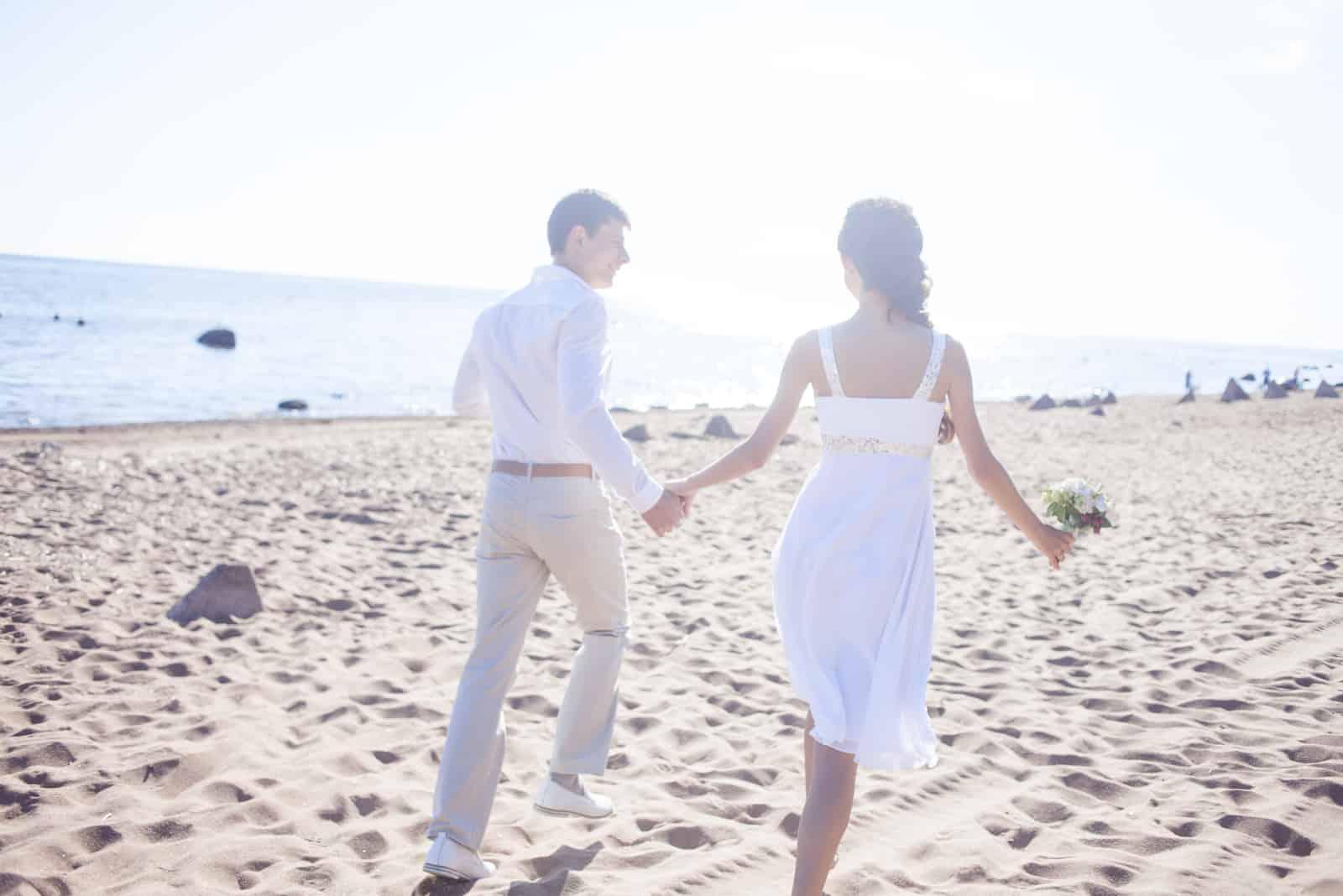 Frisch verheiratetes glückliches Paar, das an einem Sandstrand läuft