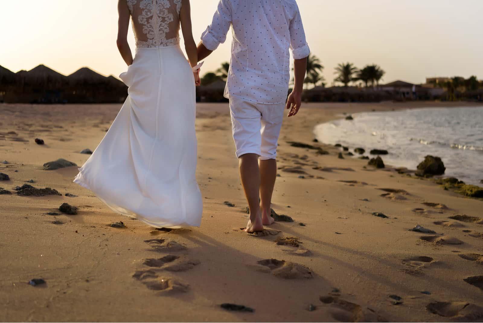 Frischvermählte gehen bei Sonnenuntergang am Strand entlang