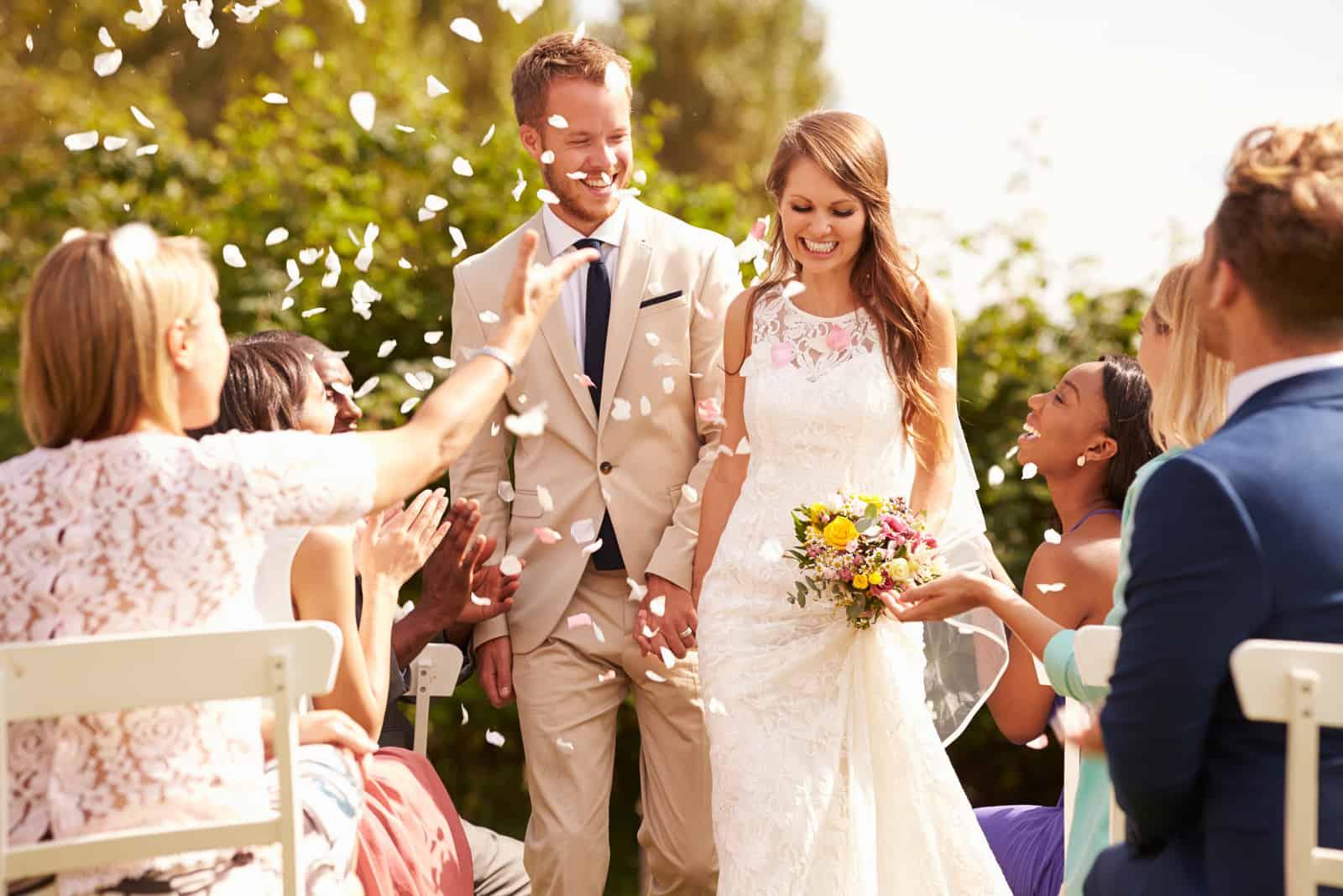 Gäste werfen Konfetti über Braut und Bräutigam bei der Hochzeit