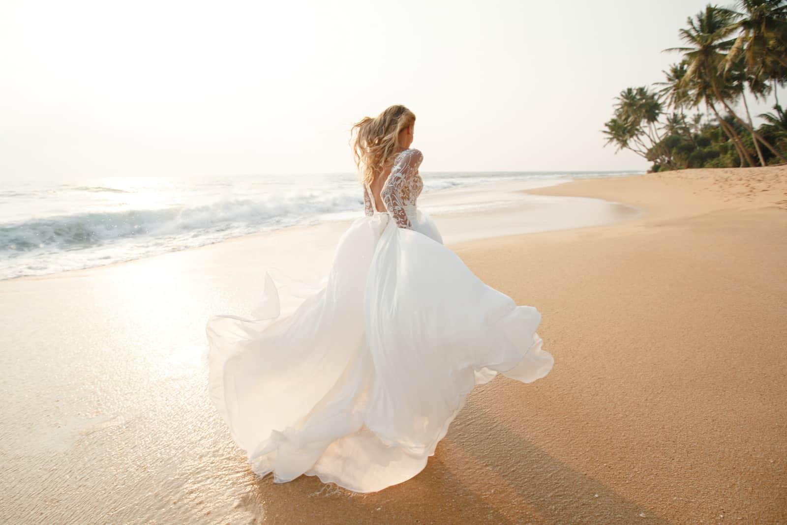 Glückliche junge Brautfrau im weißen Kleid läuft