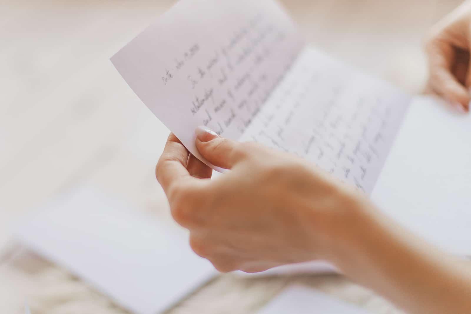 Hände der jungen Frau, die handgeschriebenen Brief hält