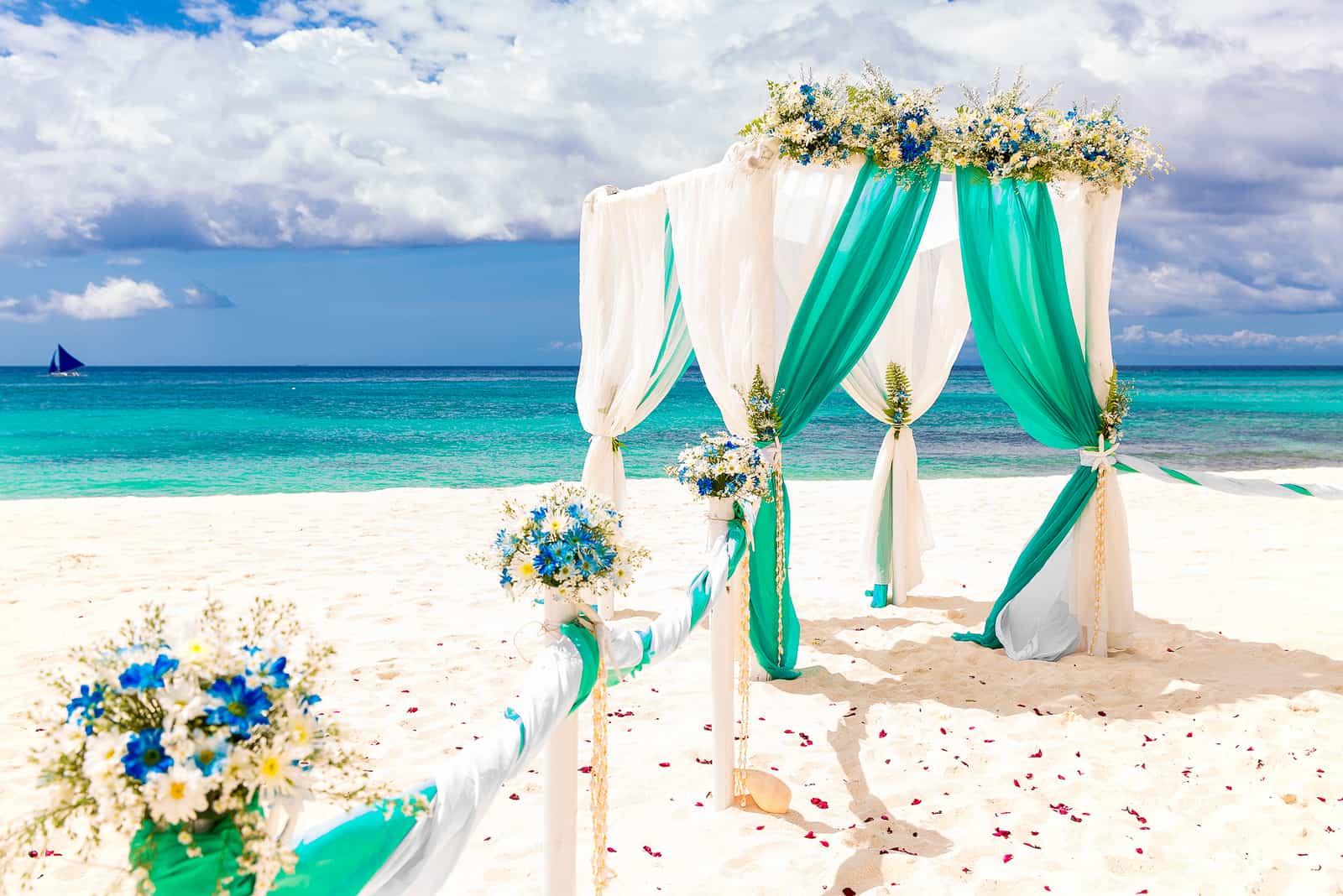 Hochzeitsbogen verziert mit Blumen am tropischen Sandstrand
