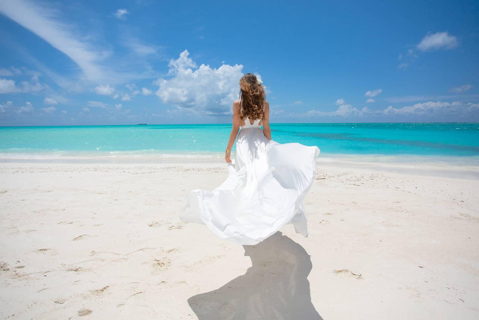 Junge Frau am Strand der tropischen Insel im weißen Kleid
