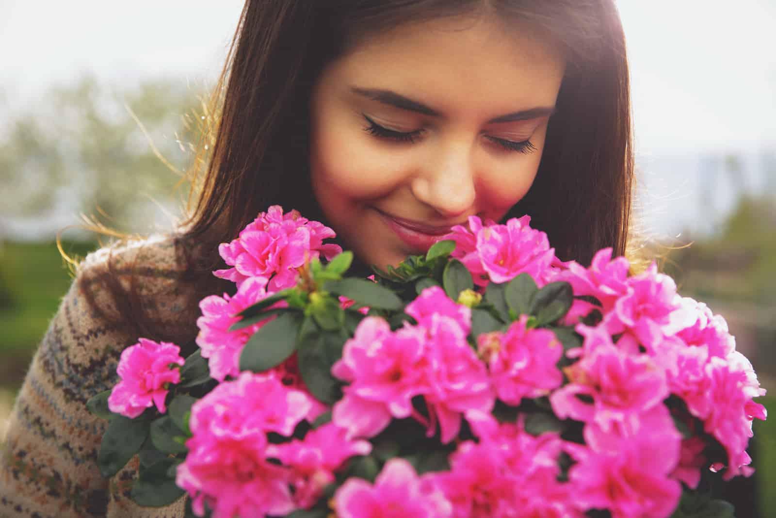 Junge süße Frau, die rosa Blumen riecht