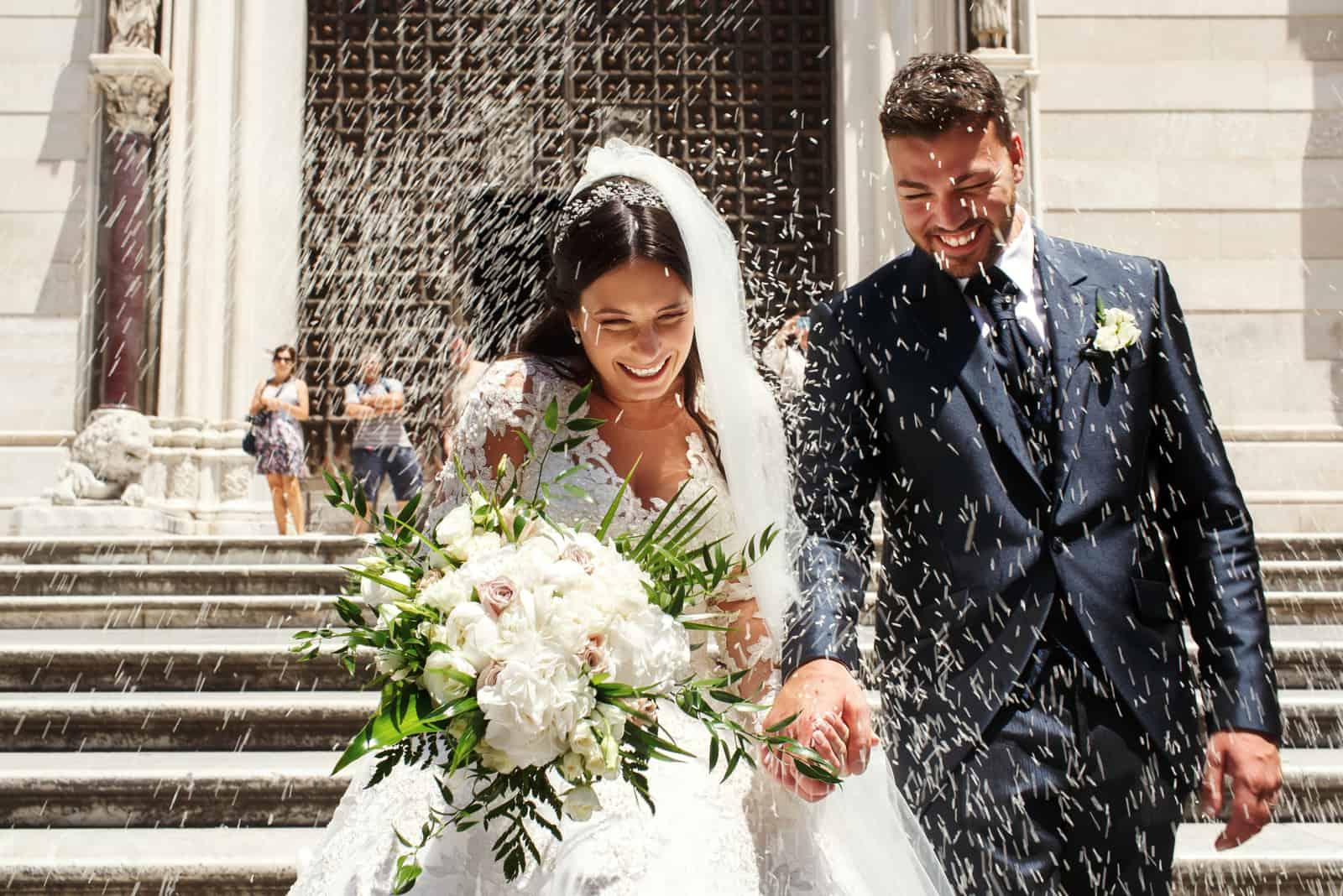 Leute bewerfen Jungvermählten, die aus der Kirche gehen, mit Reis