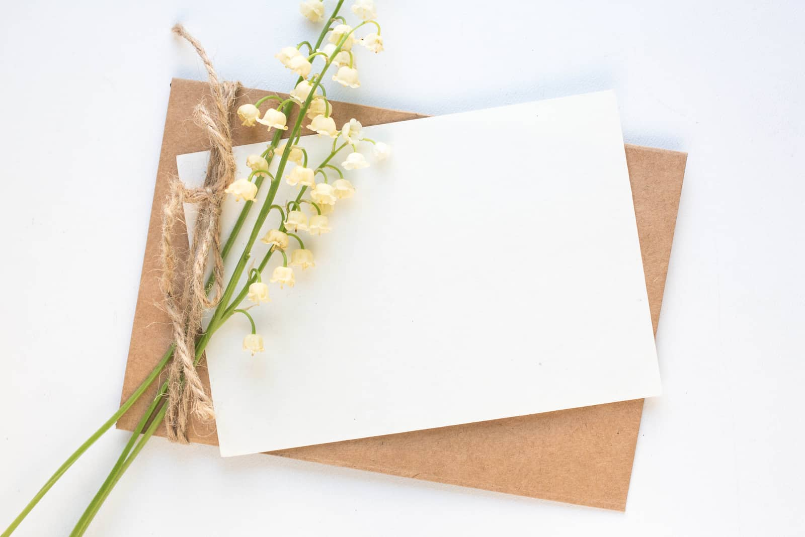 Modell mit Postkarte und Maiglöckchen auf weißem Hintergrund