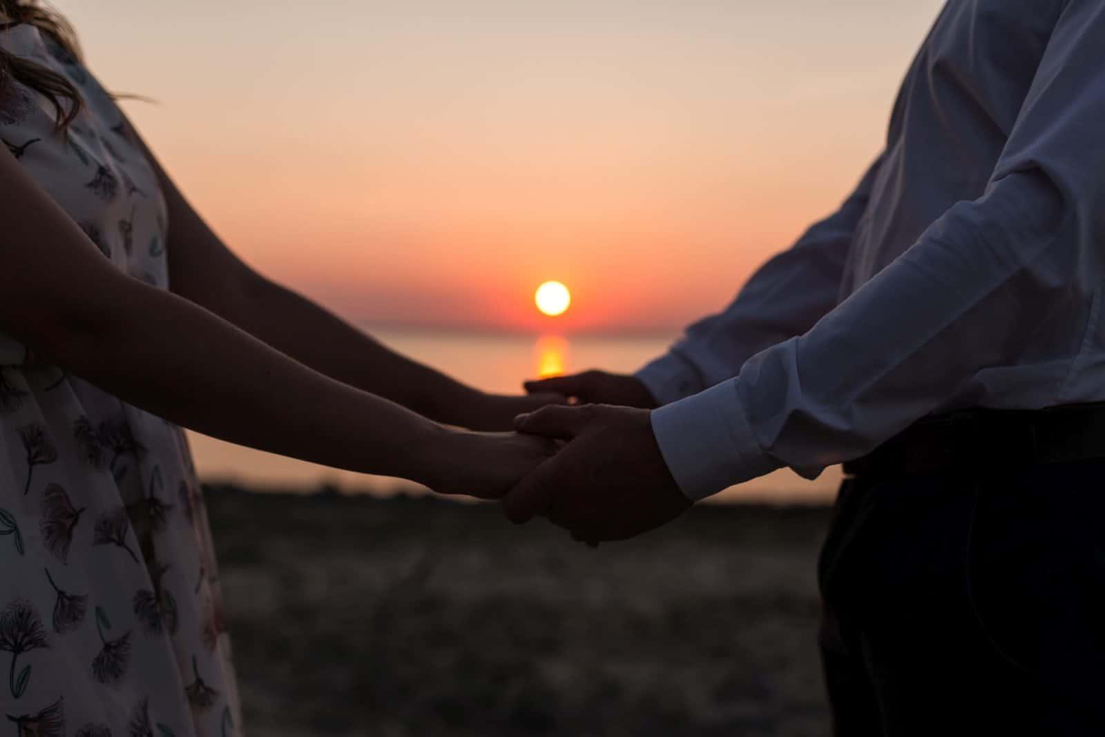 Paar Händchen haltend bei Sonnenuntergang