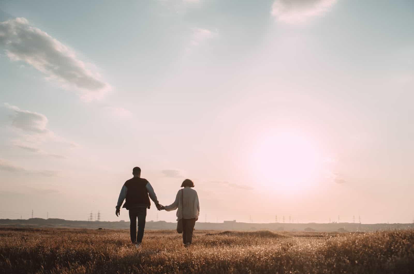 Paar geht durch das Feld und hält Händchen