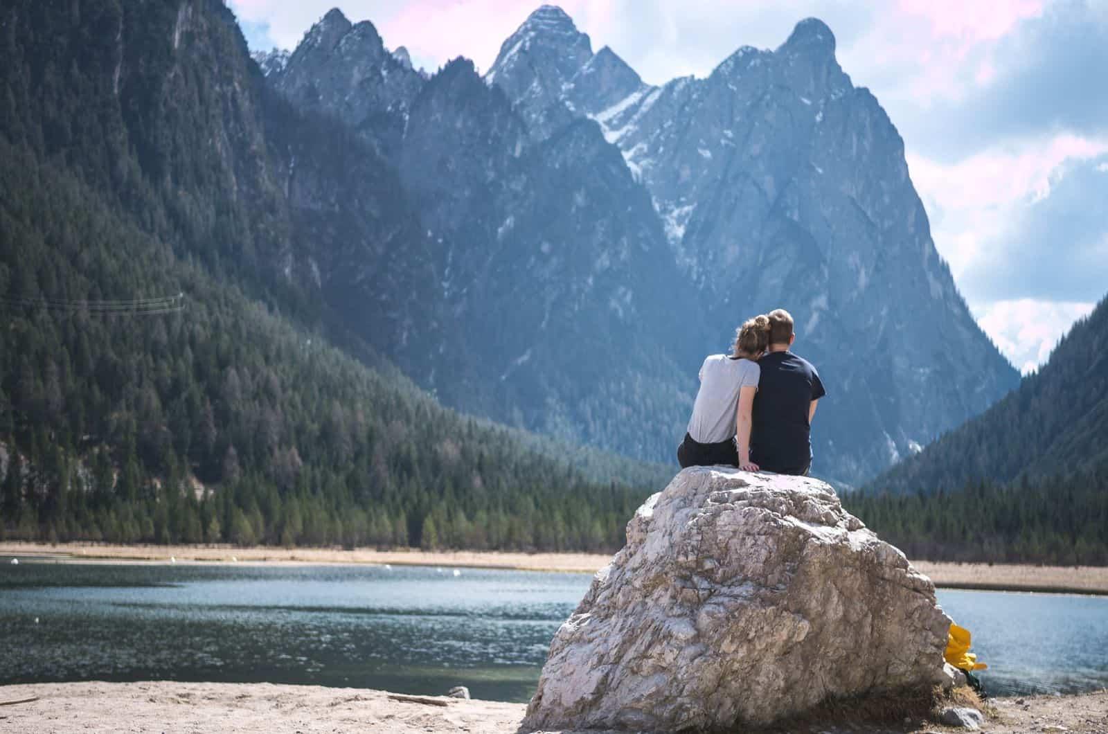 Paar sitzt auf einem Felsen in der Nähe des Sees