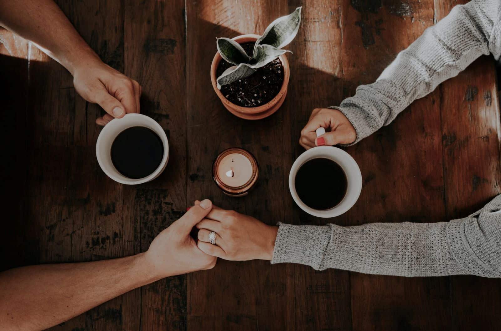 Paar trinkt Kaffee und hält Händchen